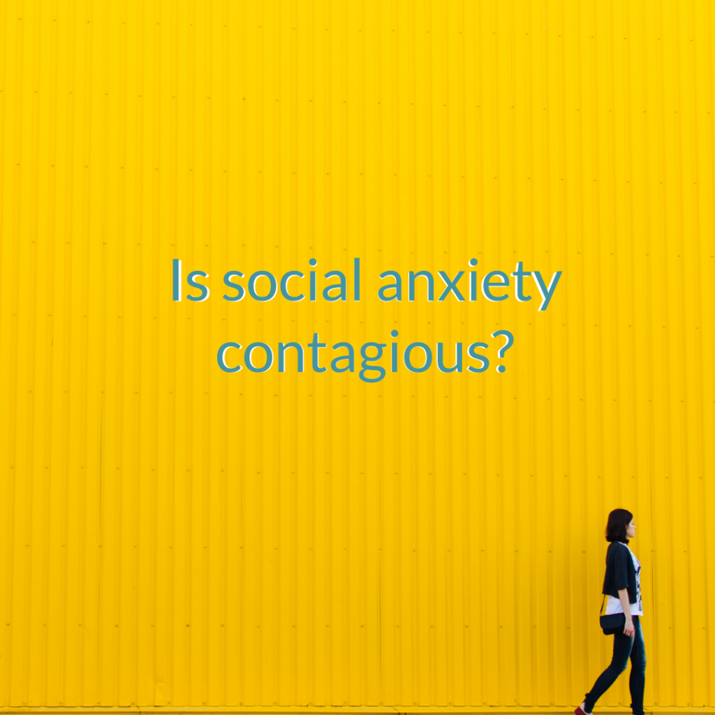 a single person walks alongside a large yellow wall. On the wall reads 'is social anxiety contagious'